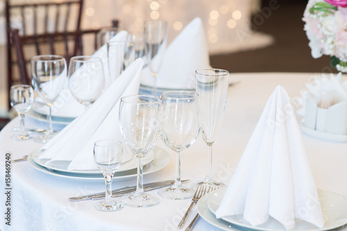 Restaurant interior for banquet, wedding. Glass, napkins and cutlery. Table appointments, laying