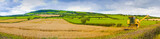 Paniramic Irish landscape with wheat field in the foreground and combine harvester (Ireland)