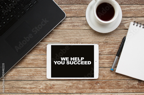 Tablet on desktop with we help you succeed text. Poster