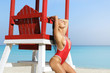Sexy woman in red swimsuit beside lifeguard tower