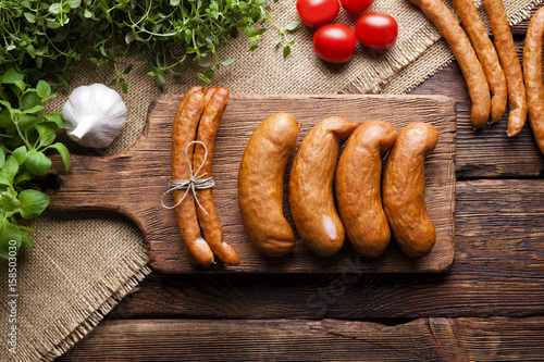 Raw sausage and vegetables on wooden and canvas background
