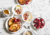 Breakfast table. Greek yogurt with cherries and honey and caramel french toast on white table, top view. Flat lay. Summer breakfast or snack