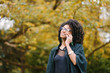 Young cheerful black woman talking on cellphone outside at the park on autumn season. Fashionable girl with afro hair.