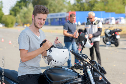Young man on motorcycle preparing to do a training course