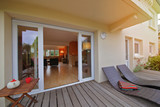intérieur salon maison rez-de-chaussée donnant sur terrasse en bois  - 158534092