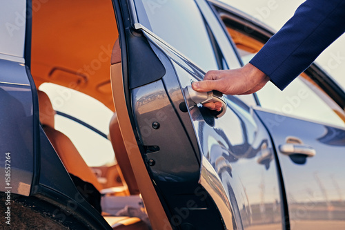 Close up image of a man opens car's door.