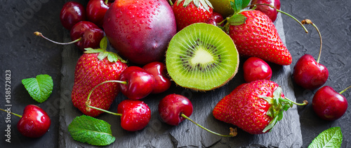 Strawberry, cherry, kiwi and peaches on black slate plate. Long banner format - 158572823