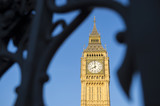 Big Ben, also known as Queen Elizabeth Tower, standing in bright blue sky behind the dark defocused silhouette of the gothic iron gates of Westminster Palace in London, United Kingdom - 158582067