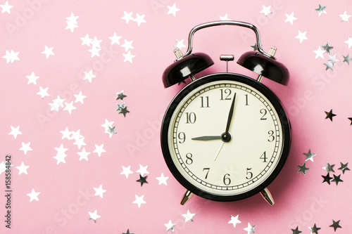 Alarm clock on the pink background
