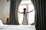 Female chambermaid opening window curtains in the hotel room - 158585650