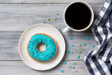 Blue donut decorated with sprinkles and cup of coffee, wooden background