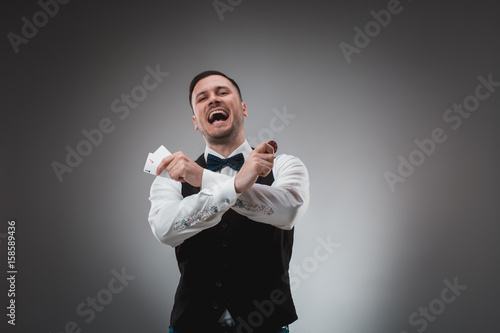 Young man in shirt and waistcoat shows his cards and holds poker chips in his ha плакат