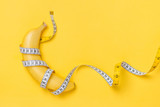 Diet, fitness and health concept presented by yellow banana wrapped in measure tape isolated on yellow paper background