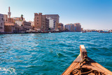 Panoramic view from traditional water taxi boats in Dubai, UAE. Creek gulf and Deira area. United Arab Emirates famous tourist destination.