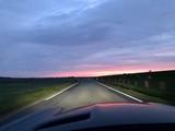 Bei Sonnenuntergang mit dem Auto auf der Landstraße unterwegs