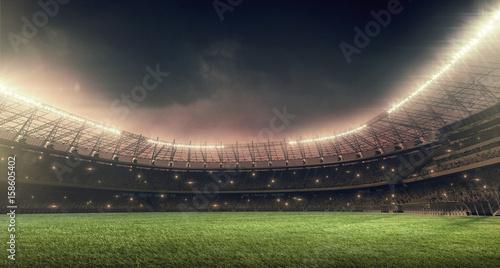 Fototapeta soccer stadium with green grass, illumination lights and dramatic night sky