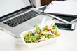 close up of fresh salad with laptop and smartphone on tabletop at workplace