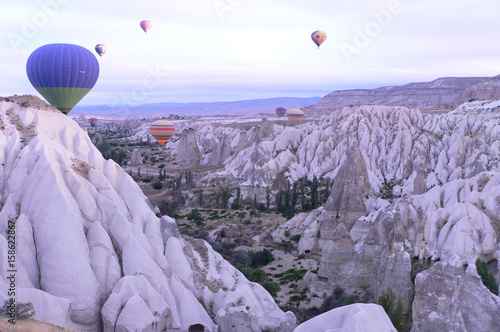 Fotobehang Purper Hot air balloon flying over rock landscape at Cappadocia Turkey