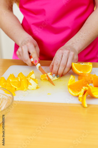Woman housewife in kitchen cutting orange fruits