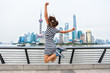 Happiness in city. Happy woman jumping of success in front of urban skyline in Shanghai, China. Winning people concept.