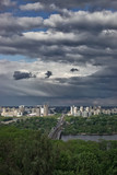 Panoramic view of the left bank of Kiev, the Dnieper river and high-rise buildings in the background of a beautiful stormy sky.