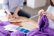 Female hands knitting a purple hat