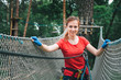 Woman climbing in forest adventure rope park
