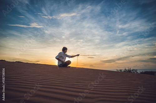 A man is pouring sand in the desert Poster