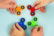 trendy fidget spinners - styled flat lay scene with hands holding colorful generic design spinners