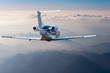 Private jet, passenger wide-body plane or aircraft is flying in the blue sky over the the clouds and mountains. Summer vacation concept