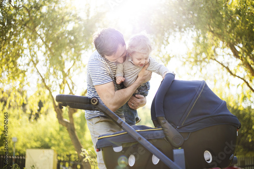Father with little son and baby daughter in stroller. Sunny park. - 158762663