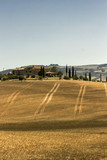 VAL D'ORCIA, ITALY - JUNE 3 2017: Tuscany Val D'Orcia landscape, view of a meadow with stripes and cypress on a hill with a rural farmhouse