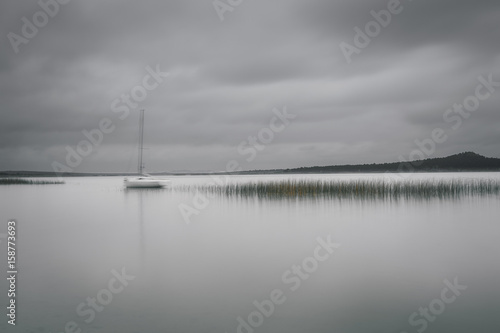 Marine landscape with moored yacht at the quiet bay. Smooth water surface at long exposure shot. Dramatic clouds over autumn lake. Reeds in the water with smooth reflection like sound wave histogram. - 158773693