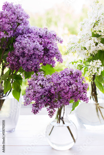 Three bouquets of lilac in round transparent vases near window Plakat