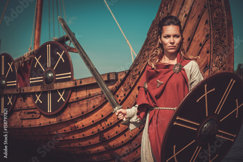 Viking woman in traditional clothes near drakkar Poster