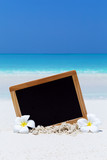 Empty blackboard on sandy beach