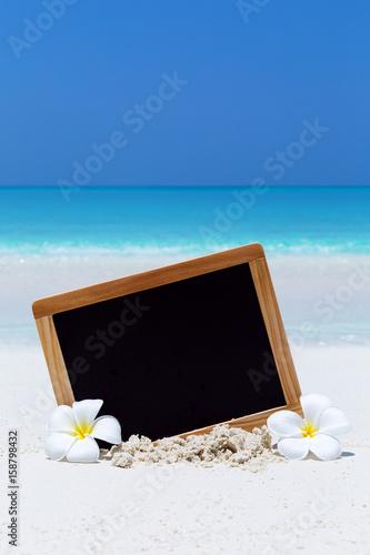 Plexiglas Plumeria Empty blackboard on sandy beach