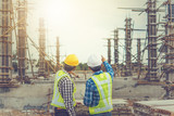 Two young man architect on a building construction site - 158804224