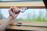 Hand opens a wooden window with silver handle