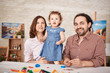 Portrait of happy family posing for photo and smiling while playing with little daughter at home