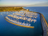 Aerial view low above Sandringham Yacht club and marina at sunset. Melbourne, Victoria, Australia