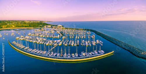 Fotobehang Purper Aerial panoramic view of moored sailboats, breakwater, and Melbourne coastline at beautiful sunset