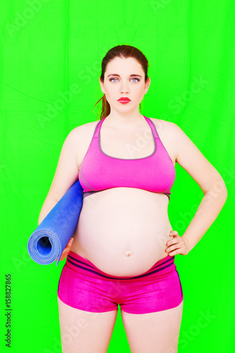 Leinwanddruck Bild Pregnancy Yoga Fitness concept. Portrait of young pregnant yoga model posing with sports mat on the green background