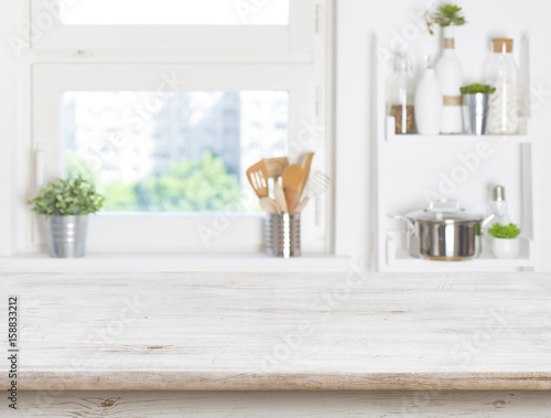 Empty table on blurred background of kitchen window and shelves - 158833212