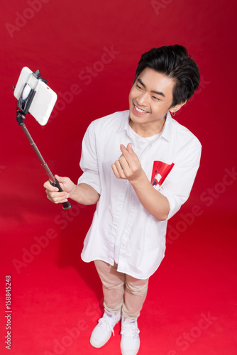 Póster Happy young asian man taking self portrait photography through smart phone over red background