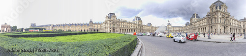 PARIS - JUNE 2014: Tourists walk near Louvre. Paris attracts 30 million tourists annually - 158857893