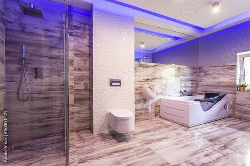 Bathroom with marble tiles and glass shower cabin - 158870421