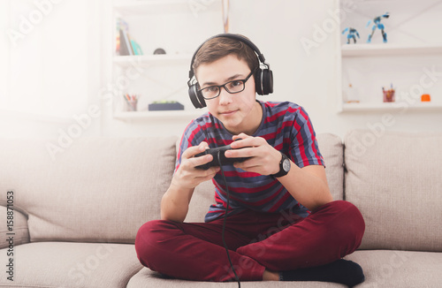 Excited teenage boy playing video game at home Poster