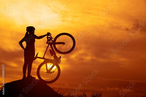 Silhouettes biker-girl na zachód słońca