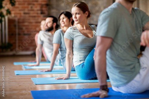Wall mural group of people doing yoga exercises at studio